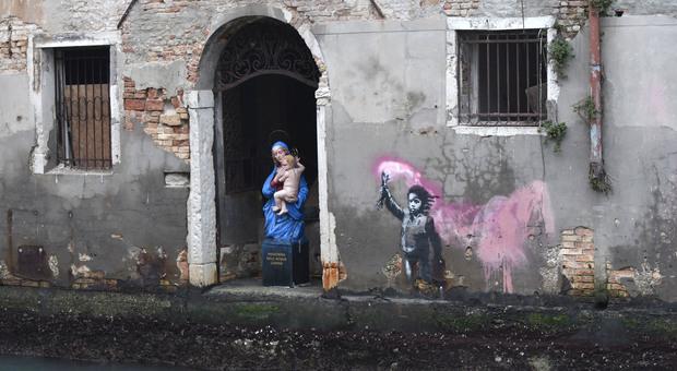 La Madonna dell'acqua lurida a fianco del murale di Banksy